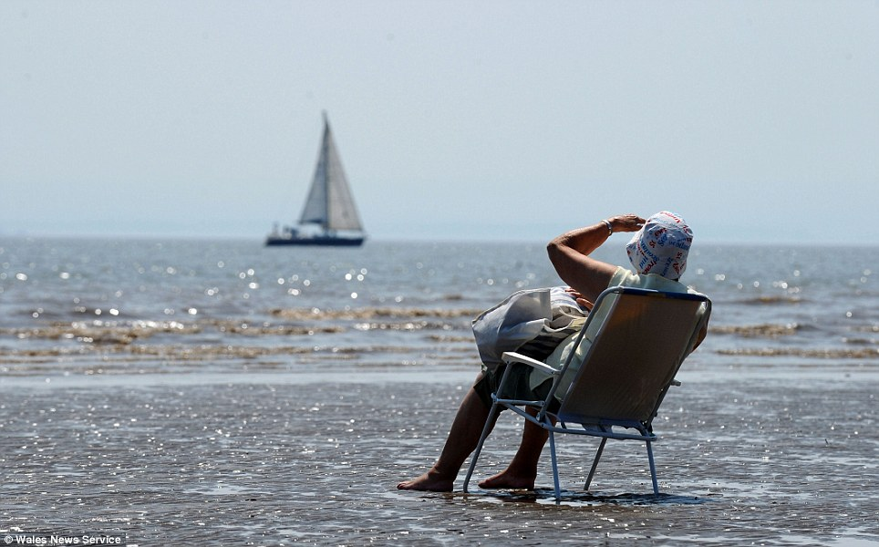 A lady shields her eyes from the sun on Barry Island Beach as Britain is hit by a heat wave