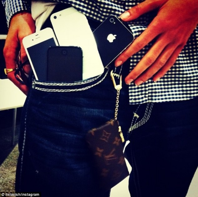 Tough times: The teenager owns so many iPhones that he struggles to fit them into his pockets