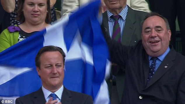 Alex Salmond raises the Scottish flag behind Cameron's head after Murray's win yesterday