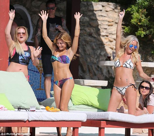 Boundless energy: The TV presenter threw her hands in the air as she danced around with her friends by the side of the pool