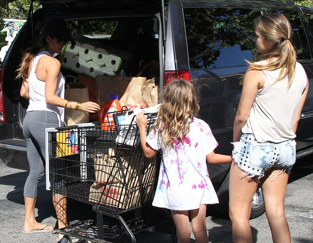 Helping hands: The kids push the cart beside Brooke so she can put their groceries away