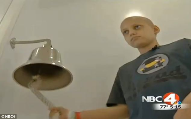 Celebration: Grant rang a bell at the hospital to mark his last round of chemo as staff cheered him