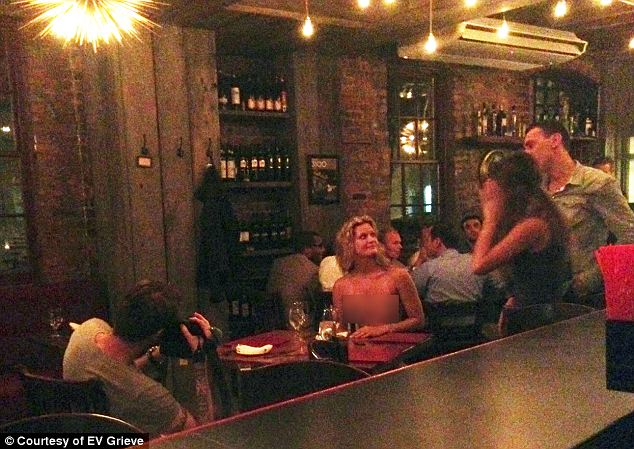 This unidentified woman walked into a restaurant, sat down clothed, then too her shirt off while a man snapped photos