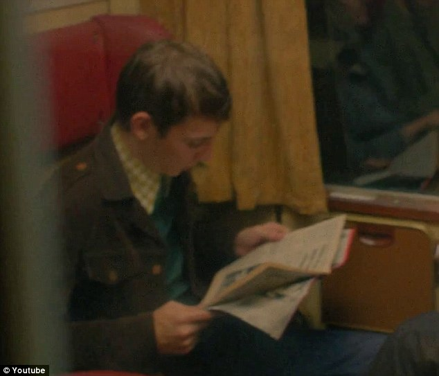 Object of her affections: This strapping young chap reading a newspaper looks set to be taken unawares