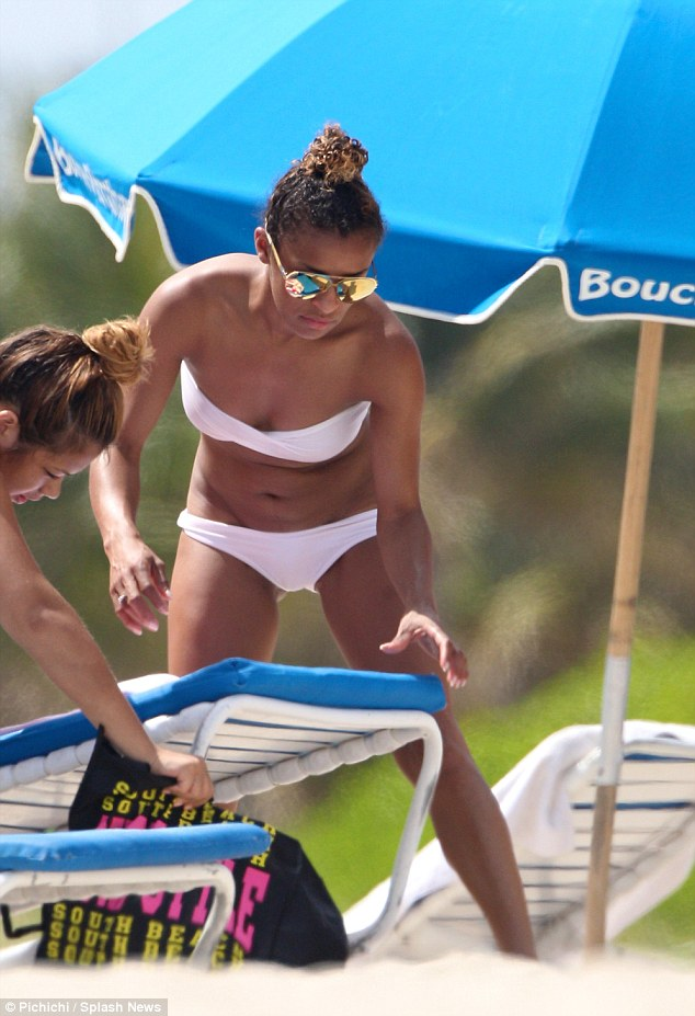 Flashy touch: Melody donned gold reflective sunglasses as she and a friend set up their sunbeds