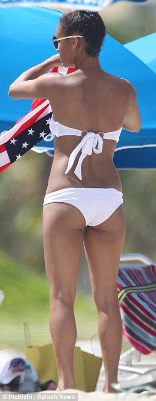 Feeling cheeky: The 28-year-old displayed her pert derriere in the flimsy suit as she got ready for some sunbathing