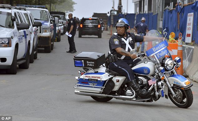 Motorcade: A Boston motorcycle police officer watches the motorcade pass. Tsarnvaev arrived in foot shackles, appearing disheveled but cocky