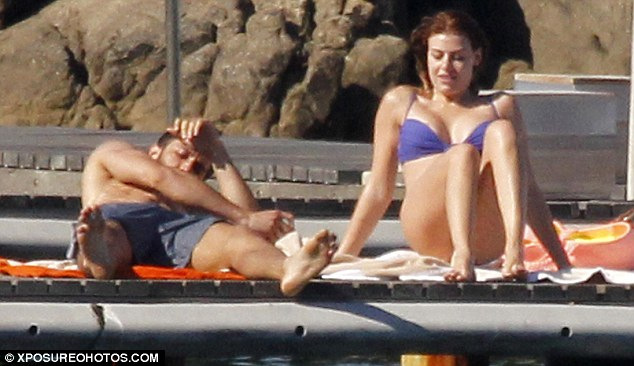 Content:  The pair look comfortable in each other's company at they sunbathe on the jetty with friends