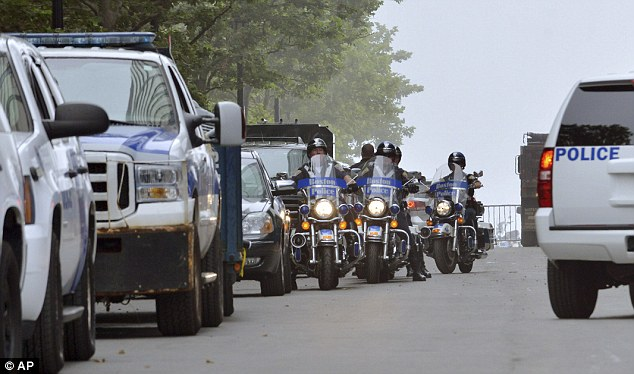 Show of Strength: Boston motorcycle police officers ride down a drive alongside the federal courthouse before the arrival of Boston Marathon bombing suspect Dzhokhar Tsarnaev for his arraignment on Wednesday