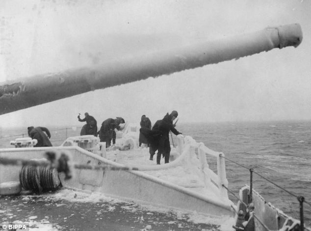 Members of a British destroyer clear the frozen deck of the ship during an Arctic convoy in the Second World War
