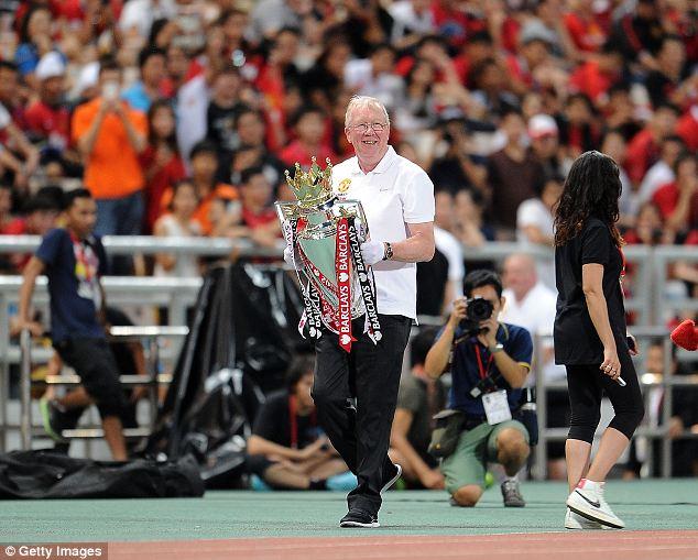 Look away, David: A look-a-like of Sir Alex Ferguson parades the Premier League trophy