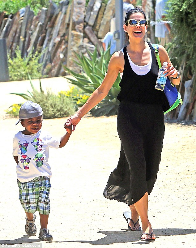 Ditching the lingerie: Sandra Bullock confessed in a new interview that she wears a cheetah onesie to bed to make her son Louis laugh, pictured together in LA in January