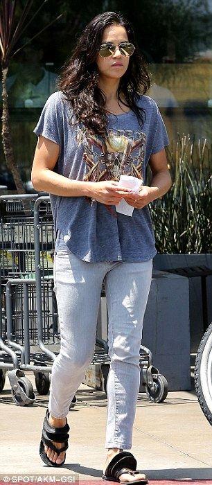 Casual comfort: The newly 35-year-old wore light blue jeans - cropped to the on-trend length of just above the ankle - with a blue loose fitting T-shirt with a pirate skull on it and chunky flip flops