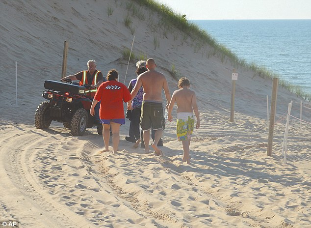 Vacationers: Family members of Nathan Reul, the 6-year-old boy who was buried in the sand at Mount Baldy are escorted to the beach by a Michigan City Police Department chaplain