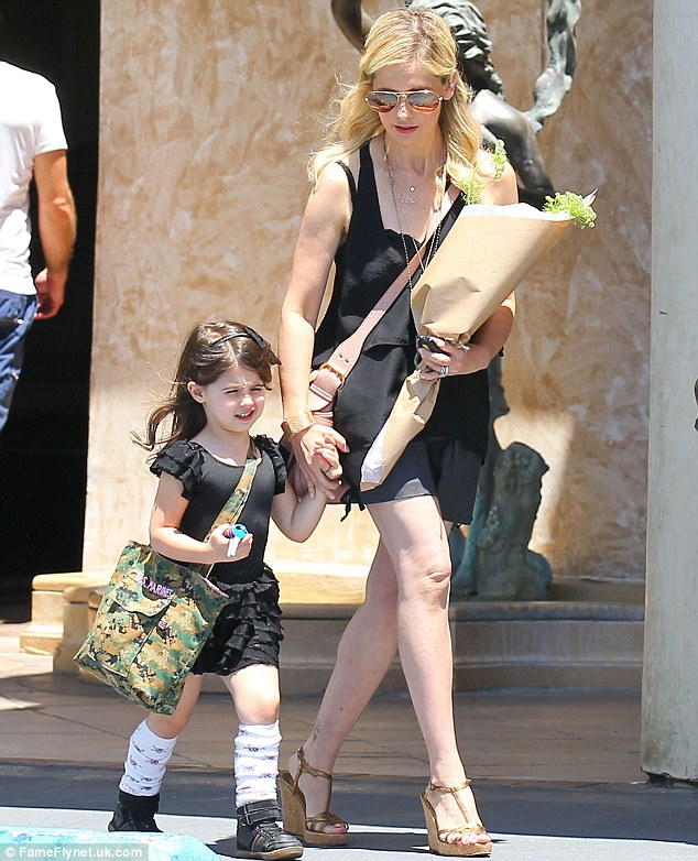 Blooming lovely: Sarah Michelle clutched a bouquet of flowers in one hand, while making sure she held onto the three-and-a-half year old