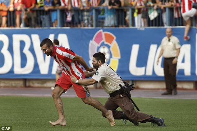 Grappled: A member of the stadium's security team tackles one supporter to the ground
