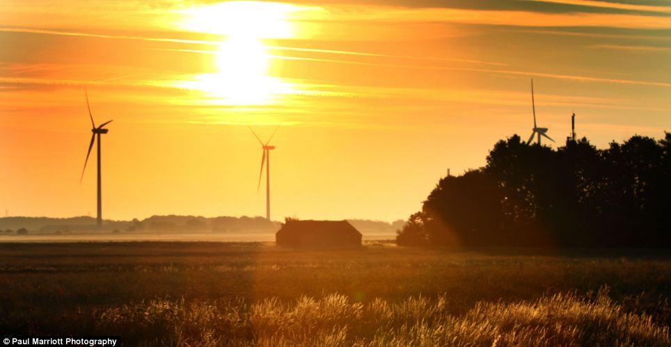 The sun rises behind these wind turbines ahead of another hot day that is expected in Peterborough, Cambridgeshire