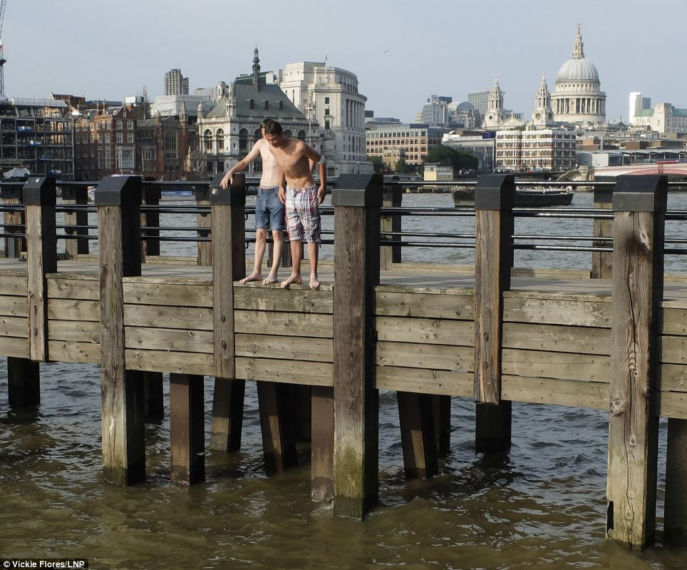Making a splash: Two men jump jump from a jetty into the River Thames on the South Bank in London today