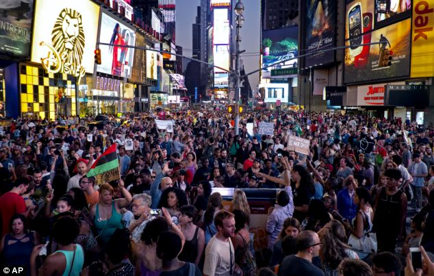 Protest: Throngs of marches arrive at Times Square in New York City on Sunday in protest of the verdict