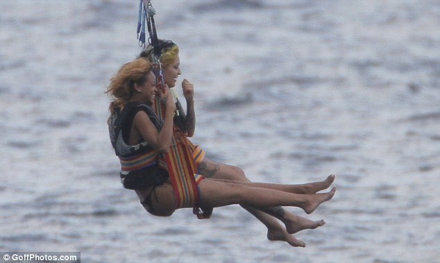 Giggles: Rihanna and her pal laughed away as they approached the water