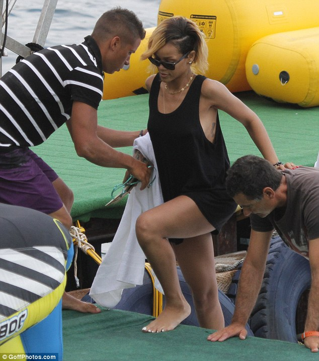 Hold on: Rihanna used one of the gentleman's backs to help her get out of the boat