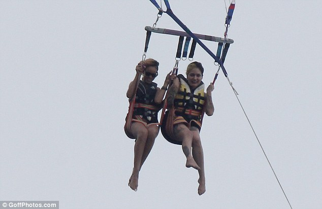 Smiles: The star couldn't stop smiling as she floated above the sea with the help of the parachute