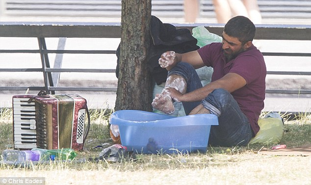 Life: One member of the camp sits under a tree and washes his feet in a plastic tub earlier this week before the camp was broken up today