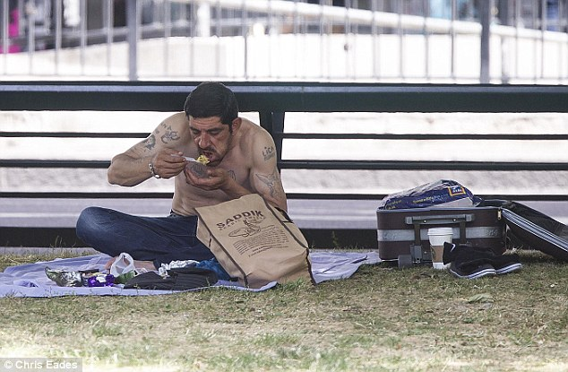 This man sat on the grass beside his open suitcase as he enjoyed a bite to eat and a Starbucks drink
