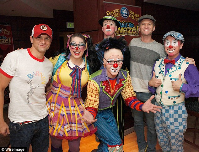 Send in the clowns: Harris and Burtka posed with an assortment of colourful circus performers