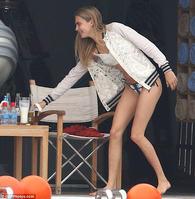Stylish in the sunshine: Cara covered up in one of her signature baseball jackets, this time a chic lace-detail number