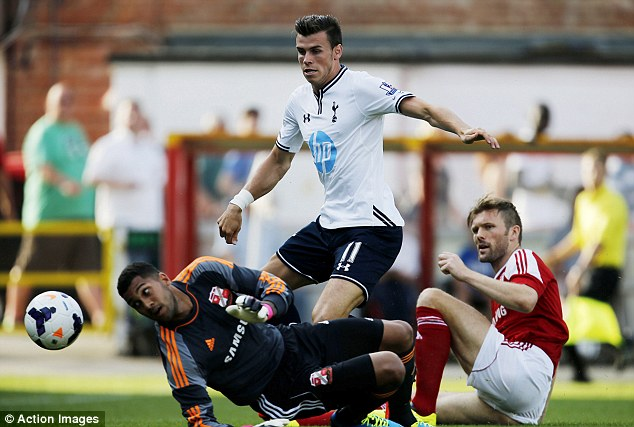 Getting stuck in: Bale battles for the ball with Darren Ward and Wes Foderingham