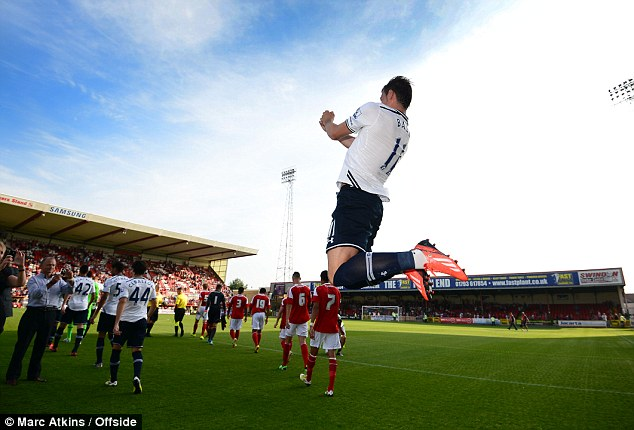 Coming out to play: Bale leaps onto the pitch at the County Ground