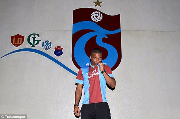 New allegiance: Florent Malouda kissing the badge of Trabzonspor