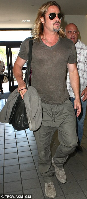 Cool customer: Brad wore aviator sunglasses, a khaki T-shirt and baggy trainers