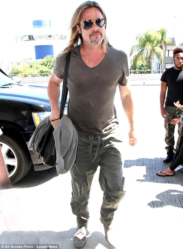 Toned and taut: Brad Pitt showed off his impressive torso in a sheer khaki T-shirt as he jetted out of LAX on Tuesday