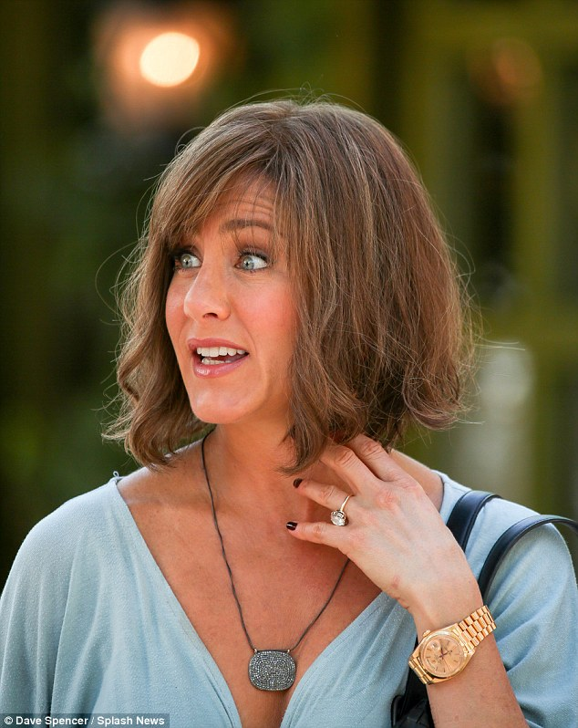 Big sparkler: Jennifer flashed her large engagement ring from fiance Justin Theroux as she waited on set