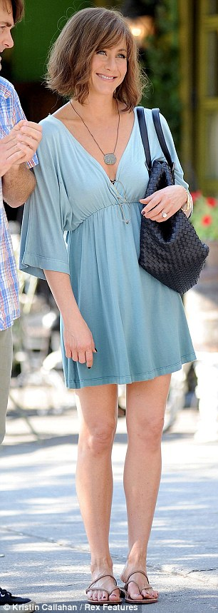Fresh as a daisy: The 44-year-old showed off her toned legs in a short empire-waist dress paired with elegant brown sandals