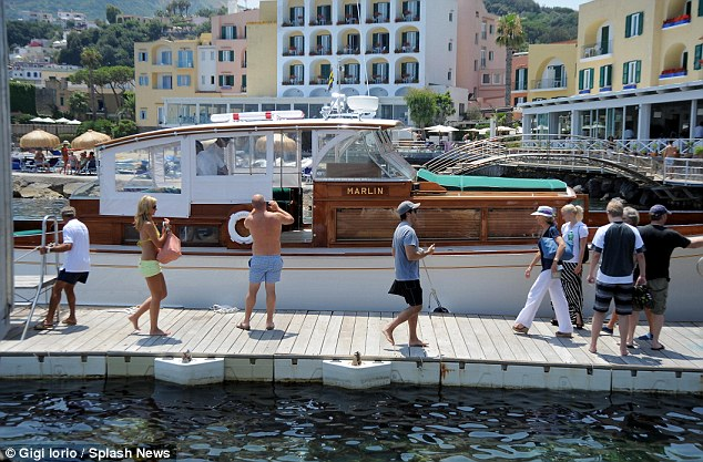 Picturesque: The Kennedy party is seen arriving aboard the Marlin, with the beautiful town of Ischia in the background