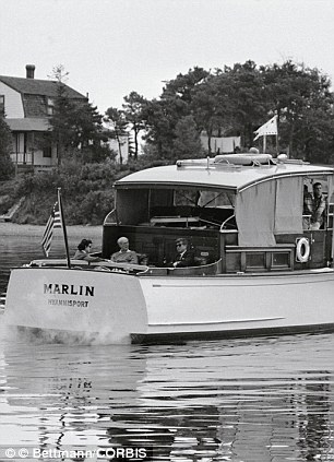 President Kennedy is shown seated in the stern of the Marlin chatting with his father former Ambassador Joseph P. Kennedy and his cousin Ann Gargan