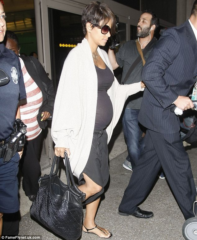 Ready to pop: Halle, who sported a black tank top which turned sheer under the flashbulbs and a matching skirt, is getting bigger by the day