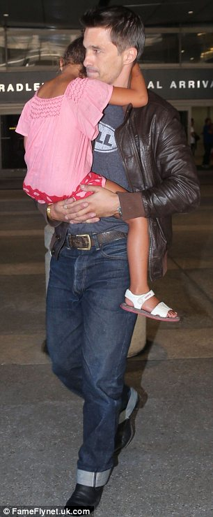 Father figure: Olivier carried his new stepdaughter through the airport as the five-year-old slept