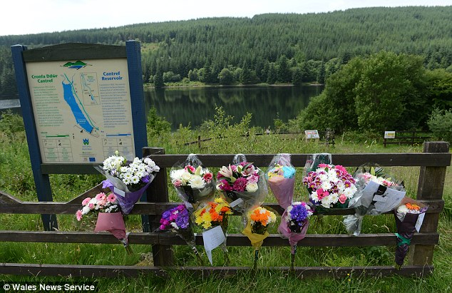 Grief: Floral tributes are left at the Cantref Reservoir where Daniel drowned on Sunday