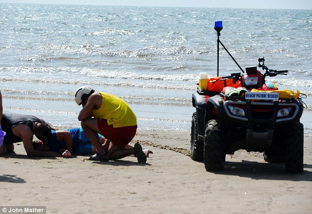 Sea rescue: A lifeguard in Blackpool, Lancashire, attends to a swimmer who got into difficulty in the water