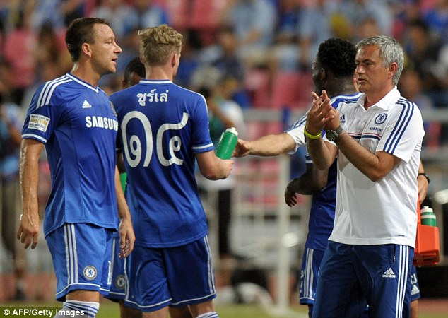 Instructions: Mourinho passes the game plan on to John Terry during a drinks break in the sweltering Bangkok heat. The Chelsea players wore their shirt names and numbers in Thai for the match