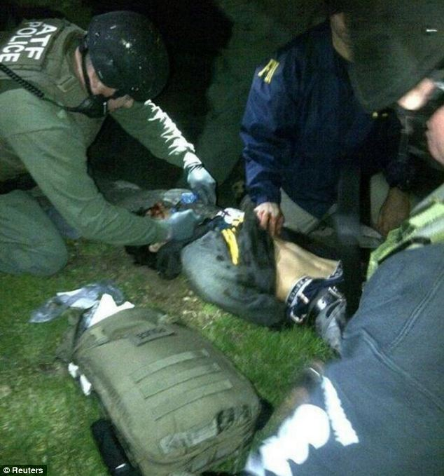 Boston bombing suspect Dzhokhar Tsarnaev, 19, is captured by law enforcement officers on April 19 after hiding out in the stern of a boat parked in the backyard of a house in Watertown