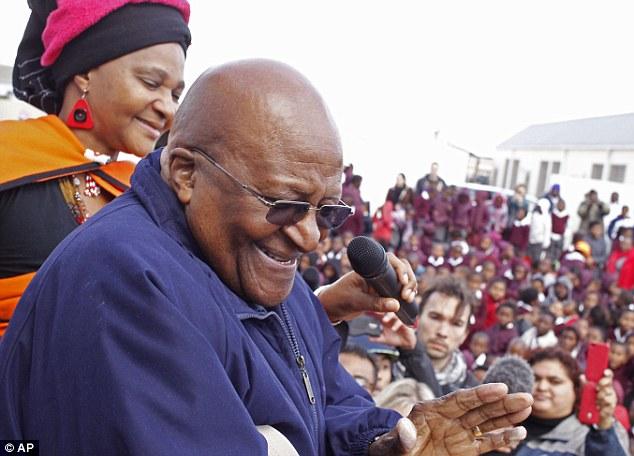 Beaming: Desmond Tutu, centre, celebrates Mandela's birthday at a school in Cape Town