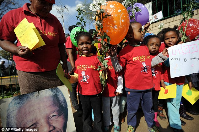 Thrilled: Schoolchildren wait to sing Happy Birthday to the iconic leader outside the hospital. Doctors today said his health is 'steadily improving'