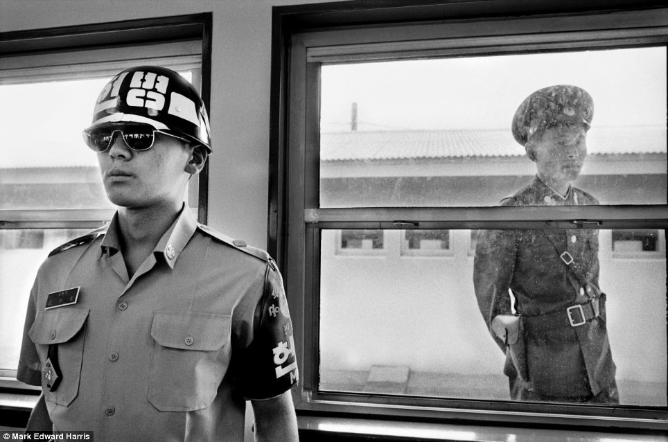 In the Demilitarized Zone between the two countries, a South Korean soldier, left, guards his side of the divide, while his North Korean counterpart looks through the window