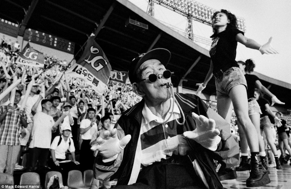 Cheerleaders wearing black T-shirts, denim shorts and platform boots lead the crowd at the Jamsil baseball stadium in Seoul