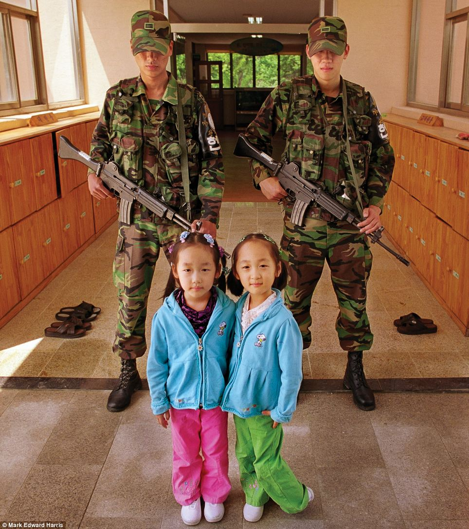 Two small girls pose in front of South Korean soldiers in Daeseong-dong, a town in the Demilitarized Zone between North and South